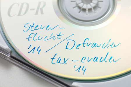 bilateral: CD with data from tax cheaters Stock Photo