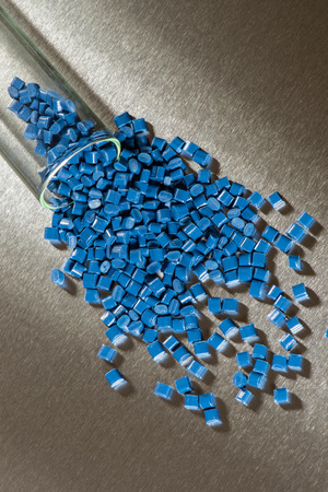 blue polymer granulate on stainless steel sheet in laboratory