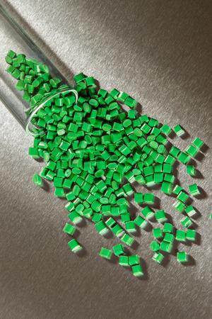 stainless steel sheet: green polymer granulate on stainless steel sheet