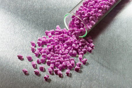 granules: pink polymer resin in test-tube on stainless steel sheet Stock Photo