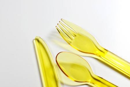 Plastik: yellow plastic cutlery made from polypropylene on white background Stock Photo