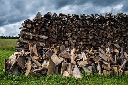 effectively: stacked fire wood on meadow under cloudy sky