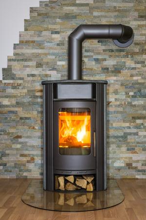 estufa: Roaring fuego dentro de la estufa de leña en el salón