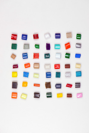 7 x 7 different polymer granulates in different colors on white in file photo