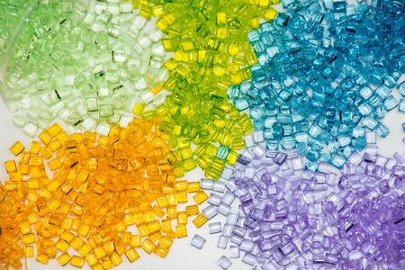 material: several different dyed polymer granulates in laboratory on table Stock Photo