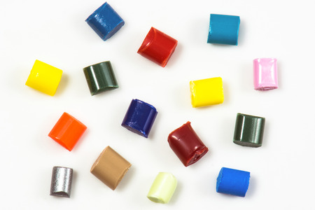 compound: close-up of fifteen different dyed plastic granulates on white Stock Photo