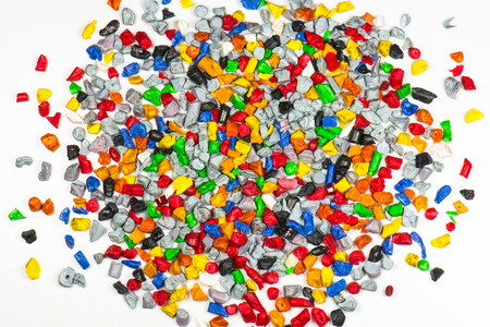 shredding: multi colored recycled polymer parts on white