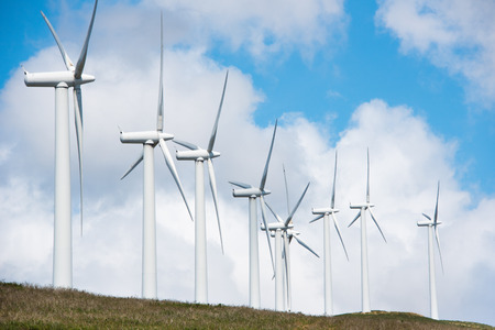 windfarms: windmill powered plant on Hilltop in Europe Stock Photo