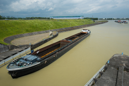 containership: empty container-vessel on river coming to a weir with lock Stock Photo