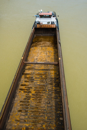 containership: empty and rusty container barge shipping on river