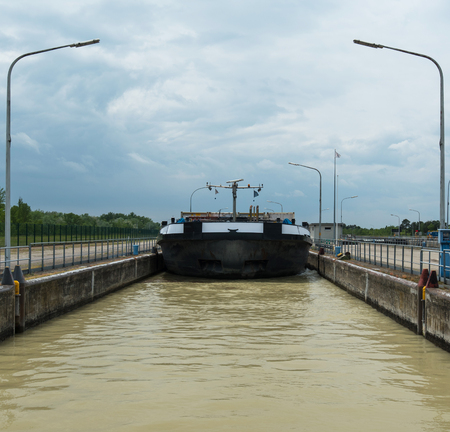 inland waterways: Container ship in barrage with lock on river