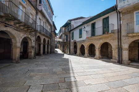orense: alley with arcaded sidewalk in Ribadavia at high noon. Galicia, northern Spain Stock Photo