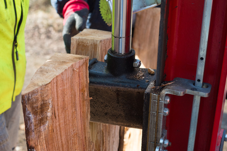 effectively: Hydraulic wood splitter at tractor machine in forest