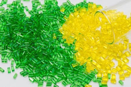 Yellow and green translucent polymer granulates an white in lab with test glass Imagens