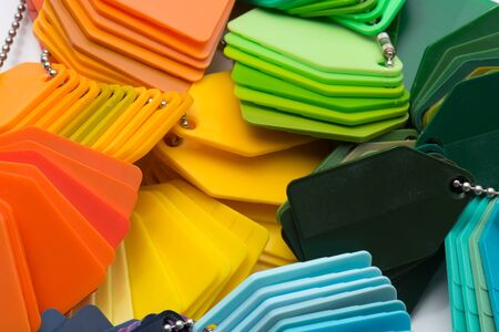 different dyed plastic pattern plates in blue, green, yellow, orange, Stockfoto