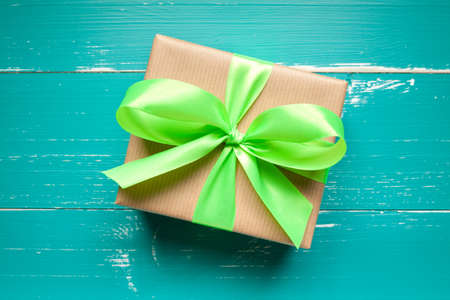 Gift box with green ribbon on turquoise table. This file is cleaned and retouched. 免版税图像