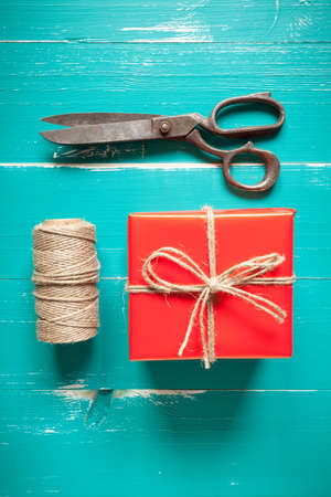 Gift box, scissors and cord on turquoise table. This file is cleaned and retouched.