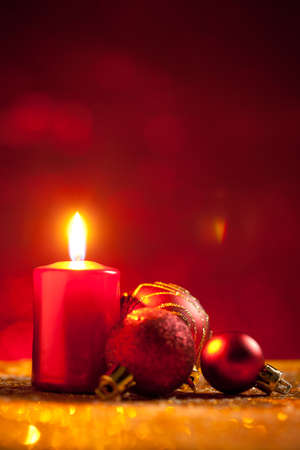 Candle and baubles on glitter with red background. On top of image is empty space to put text or something else. This file is cleaned and retouched.