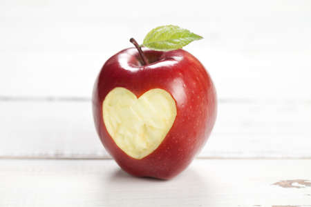 Apple with heart on old white table. On left and right is empty space to put text or something else. This file is cleaned and retouched.