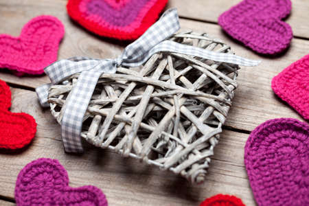 Crochet and wicker hearts on wooden table. This file is cleaned and retouched.