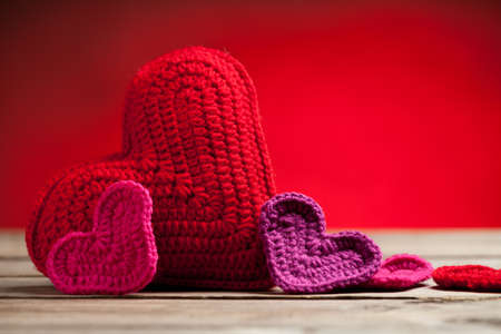 Close up of crochet hearts on old wooden table with blurred background. On the right side of image is empty space to put text or something else. This file is cleaned and retouched.