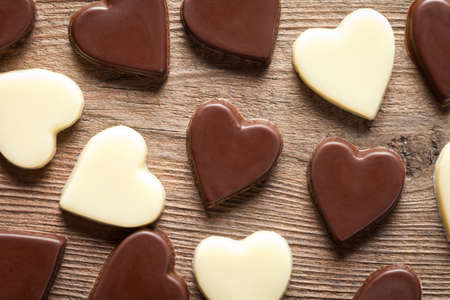 Chocolate hearts on old wooden table. This file is cleaned and retouched.