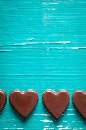 Chocolate hearts on old turquoise table. On top is empty space to put text or something else.This file is cleaned and retouched.