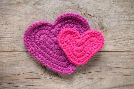 Close up of crochet hearts on old wooden table. This file is cleaned and retouched.