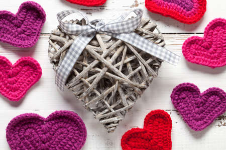 Crochet and wicker hearts on white table. This file is cleaned and retouched. Stock fotó