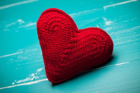 Red crochet heart on turquoise table. This file is cleaned and retouched.