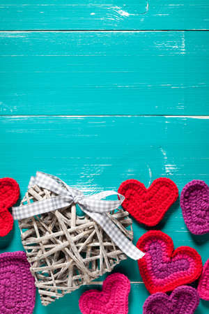 Crochet and wicker hearts on turquoise table. On the top of image is empty space to put text or something else.This file is cleaned and retouched. Stock fotó