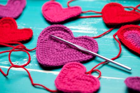 Close up of crochet hearts on turquoise table. This file is cleaned and retouched.