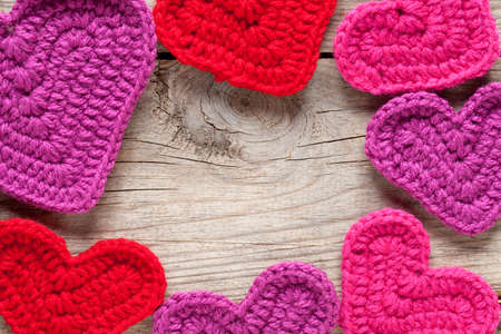 Crochet hearts on old wooden table. In center of image is empty space to put text or something else. This file is cleaned and retouched.