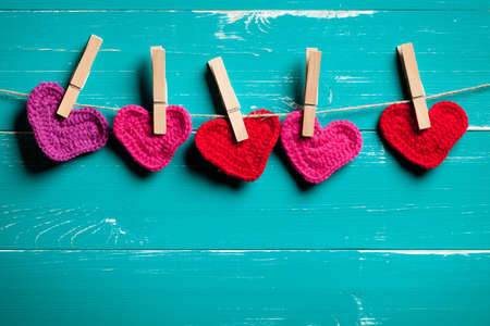 Crochet hearts on the clothesline with turquoise wood background. At the bottom of image is empty space to put text or something else. This file is cleaned and retouched.