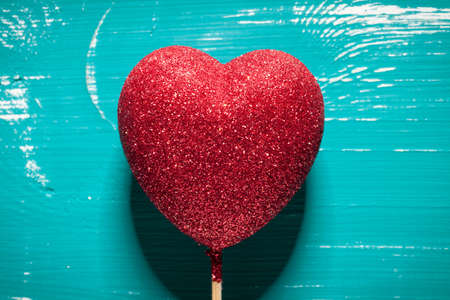 Close up of glitter heart on turquoise table. This file is cleaned and retouched.