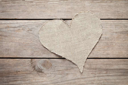 Linen heart on old wooden table. This file is cleaned and retouched.