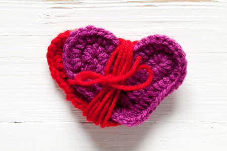 Close up of tied crochet hearts on old white table. This file is cleaned and retouched.