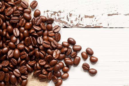 Close up of coffee beans on white wood. This file is cleaned and retouched.