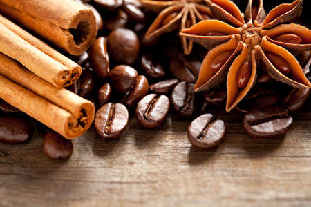 Coffee beans, cinnamon and anise on old table. This file is cleaned and retouched.