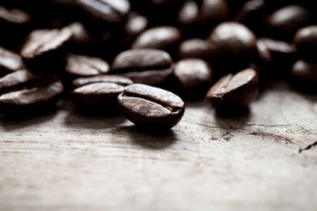Close up of coffee beans on old wood. This file is cleaned and retouched.
