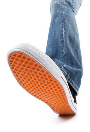 Leg with jeans trousers and black sneaker on white background - shot with wide angle lens. This file is cleaned, retouched and contains clipping path.