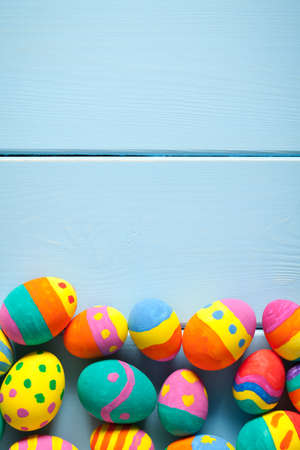 Colorful easter eggs on blue wooden table. On the top is empty space to put text or something else. This file is cleaned and retouched.