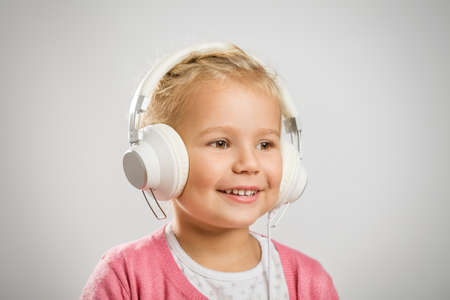 Cute little girl listening music on headphones. This file is cleaned and retouched.