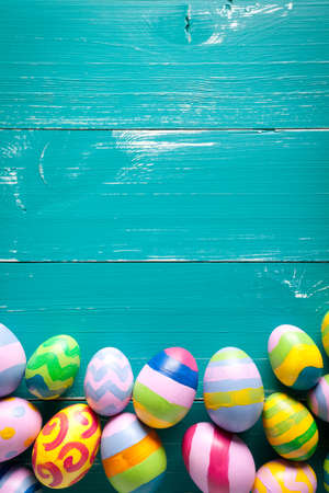 Colorful easter eggs on turquoise wooden table. On top of image is empty space to put text or something else. This file is cleaned and retouched.