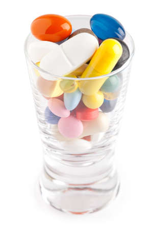 Glass full of pills on white. This file is cleaned, retouched and contains clipping path.