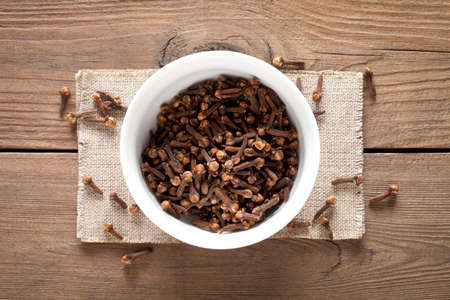 Close up of cloves in cup on old wooden table. This file is cleaned and retouched.