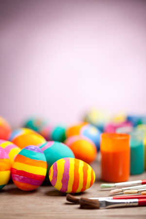Colorful easter eggs with paint on wooden table with blurred pink background. At the top of image is empty space to put text or something else. This file is cleaned and retouched.