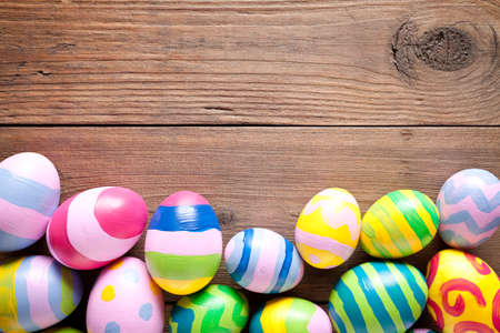 Colorful easter eggs on old wooden table. On top is empty space to put text or something else. This file is cleaned and retouched. 版權商用圖片