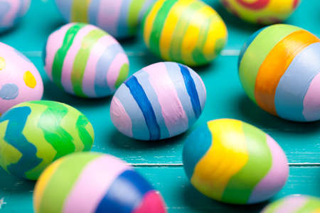 Colorful easter eggs on turquoise wooden table. This file is cleaned and retouched.