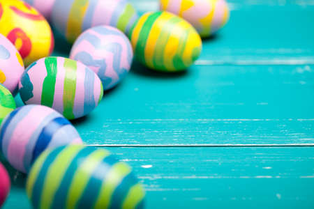 Colorful easter eggs on turquoise wooden table. On right is empty space to put text or something else. This file is cleaned and retouched. 版權商用圖片